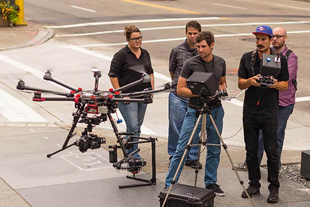 A film crew  with a drone pilot and his drone.