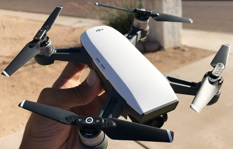 A person holding a white color DJI Spark drone in his hand.