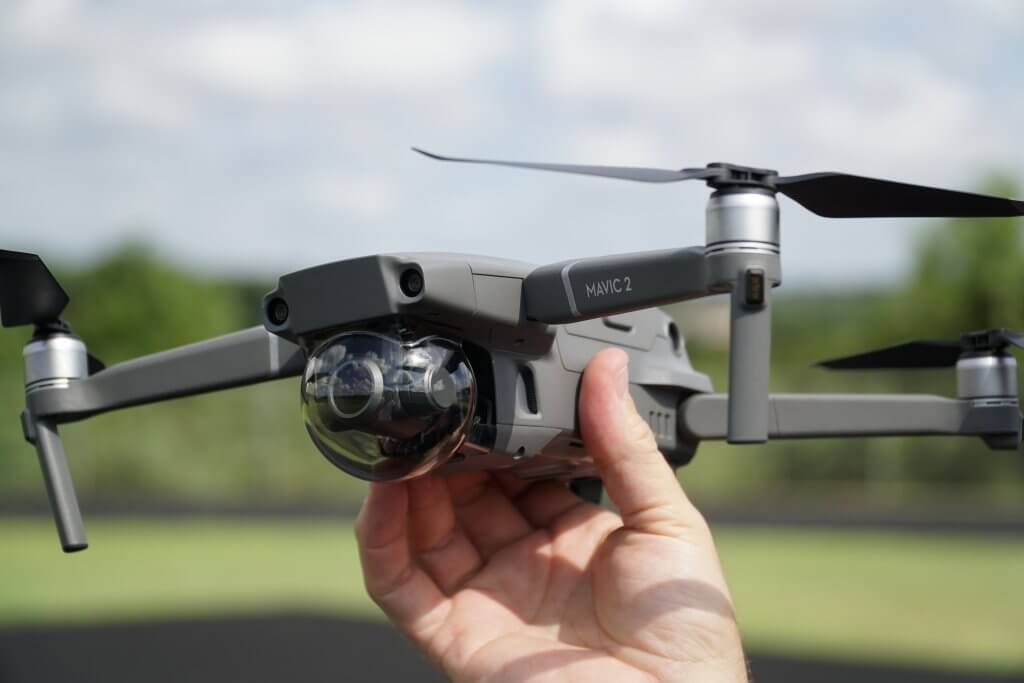 A person holding DJI Mavic 2 Zoom drone in his hand