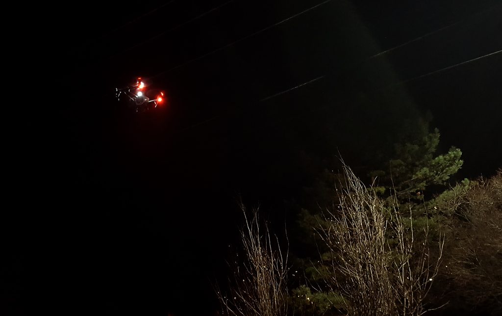 Drone with red lights flying at night