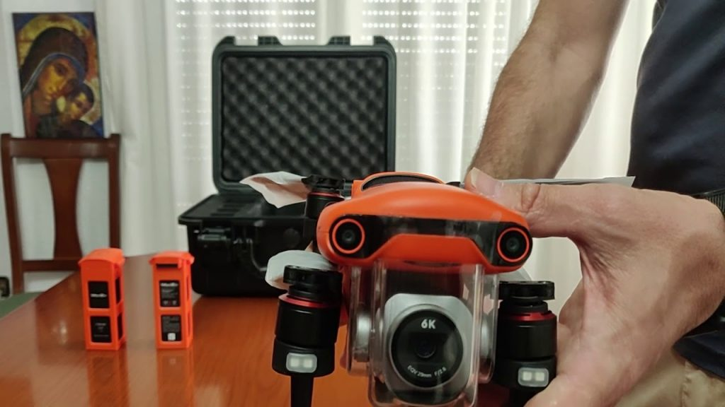 A person holding Autel Evo 2 drone with the batteries behind.