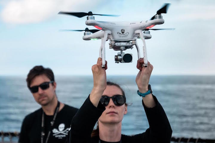 A woman holding a drone so it can take off